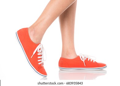 Women feet wearing red fashion sneaker shoes in hipster style, step with side view, Isolated on white background, Women's Fashion concept.