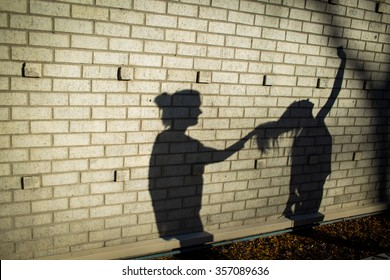 women fight and pull hair. Shadows on the wall.