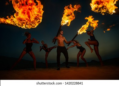 Women are fighting with man and he is defended with burning torches  in the night on sand dunes
