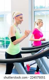 Women in fitness gym doing sport running on treadmill