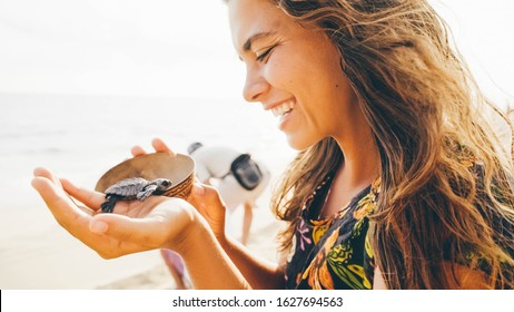 Women with flapping hair hold wooden bowl with newborn turtle, close up portrait girl at the turtle sanctuary hatchery located on the beach.