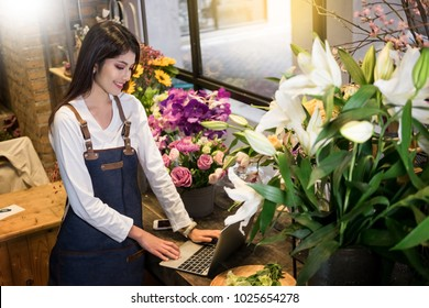 Women florist looking laptop got order at counter of her flower shop, occupation working concept