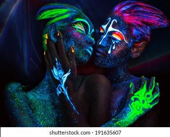 Women with fluorescent body art. Black background.
