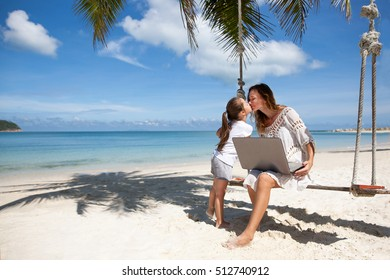 Women freelance on a beach with laptop. Resting with her child.