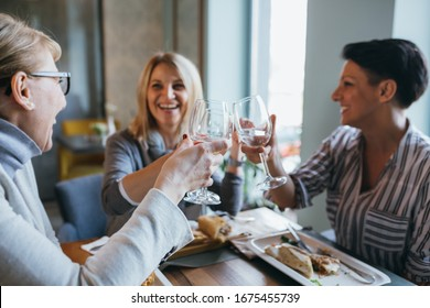 women friends making toast with wine in restaurant