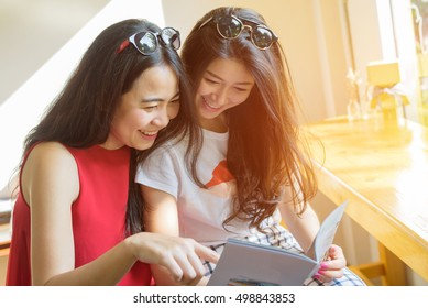 women friends reading book in outdoor coffee cafe - young female student friendship lifestyle portrait best friends