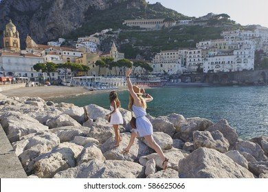 Women friends travel in beautiful Italy relaxing summer vacation exploring to discover coastal lifestyle