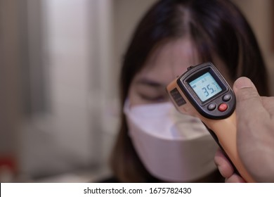 women get a fever with a laser thermometer. Show the temperature at 35.1 degrees Celsius,coronavirus prevention.