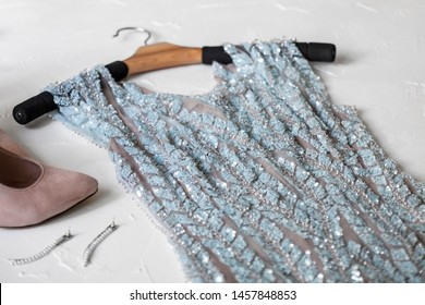 Women Get ready to prom or date or celebration flatlay top view on white background. Blue evening beaded luxury dress on hanger with earrings and shoes
