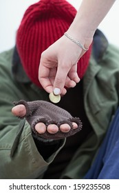 Women giving a coin for homeless poor man