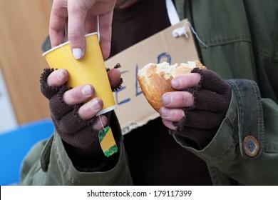 Women giving hot tea to poor homeless man