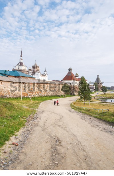 Women go down the dirt road from the Solovetsky Holy Transfiguration Monastery at summer