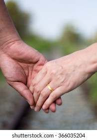 Women with golden ring hold a men hand