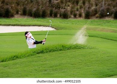 The women golfers hit golf balls off the sand motion blur