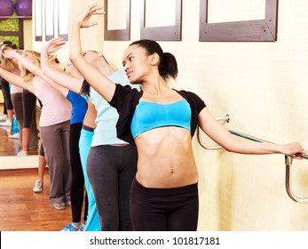 Women group in aerobics class do exercises .