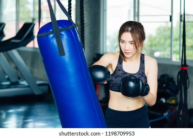 Women in gym clothes are punching sandbag in gym.