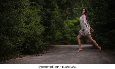 women is hailing a car on a road. Thumbing a ride. Outdoors vacation. Asian