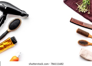 Women hair care set. Comb, shampoo, spray, curlers, hairdryer on white background top view copyspace