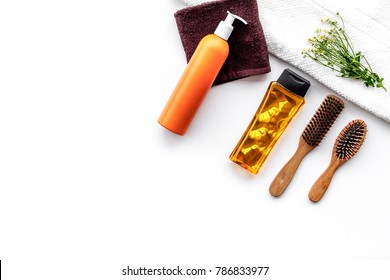 Women hair care set. Comb, shampoo, spray, towel on white background top view copyspace