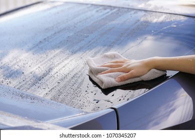 women hand dry wiping car surface with microfiber cloth after washing.