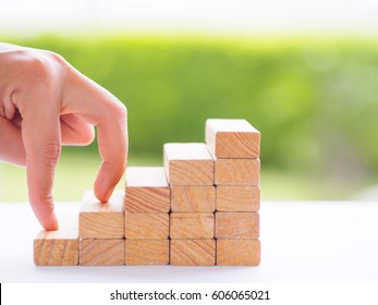 Women hand finger walk on stacked wooden block like stairs. Business development and growth concept.