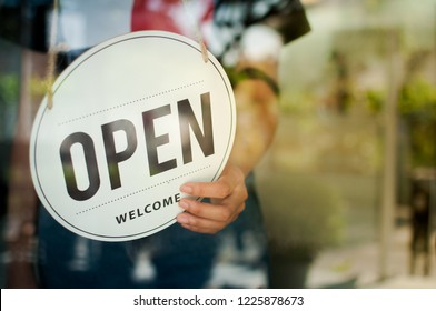 Women hand flip the sign to open the shop. Open sign hanging on the glass door.