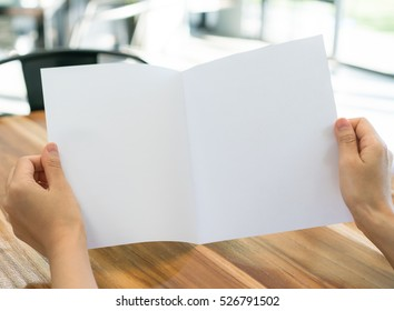 Women hand hold Bifold white template paper on wood texture