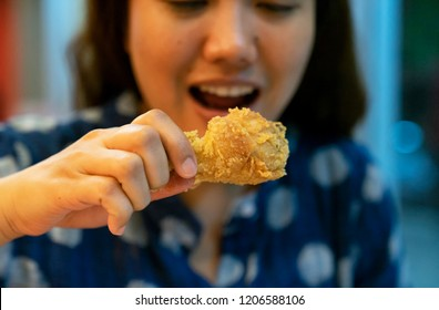 women hand hold fried chicken for eat , with fast food concept and diet