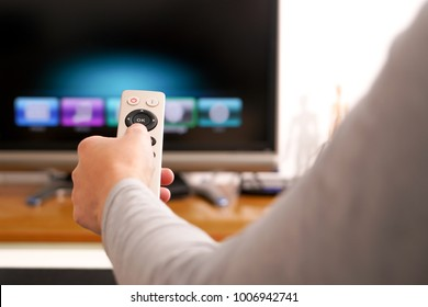 a women hand hold the remote control of the TV box in the living room