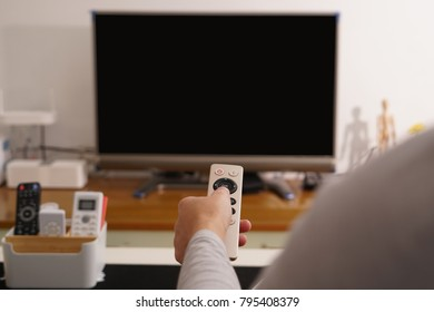 a women hand hold the remote control of the TV box in the living room the black screen TV