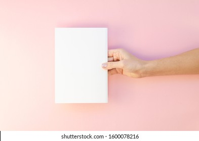 Women hand hold white template paper or magazine on pink background. Mockup flat lay with copy space