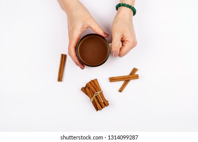 Women hand holding a cup of fresh roasted coffee, ceramic cup and cinnamon sticks