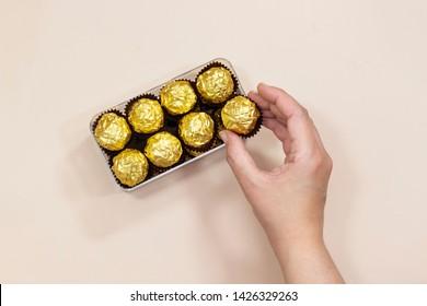 women hand holding golden premium chocolate sweets