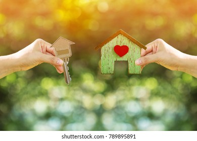 Women hand holding a home with red heart and a house-shaped keys filed together on nature bokeh in the public park, Loan for buy a house and real estate concept