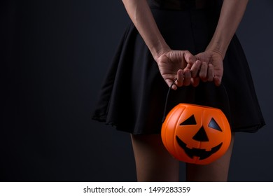 Women hand holding Jack'O pumpkin basket to collect candy trick or treat on Halloween day. Concept for Halloween holiday. Halloween festival