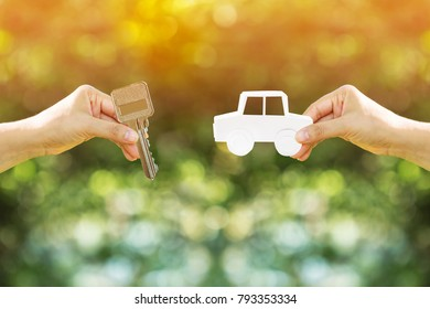 Women hand holding a key and a car with paper art filed together on nature bokeh in the public park, Loan or save money for buy a new car and a chattel concept.