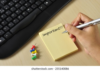 """Women Hand Holding Pen Writing """"IMPORTANT"""" On Yellow Notepad At Office Workplace, Selective Focus"""