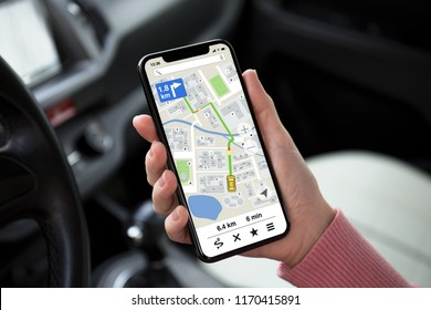 women hand holding phone with app navigation map on screen in the car