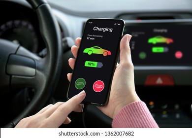 women hand holding phone in eco electric car touch multimedia system with charging battery on the screen