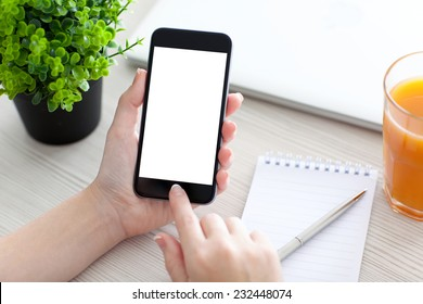 Women hand holding the phone with isolated screen above the desk