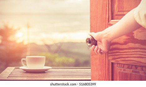 Women hand open door knob or opening the door view coffee espresso on wood table nature background in garden,warm tone