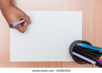 Women hand with pen write on blank paper on wood table background