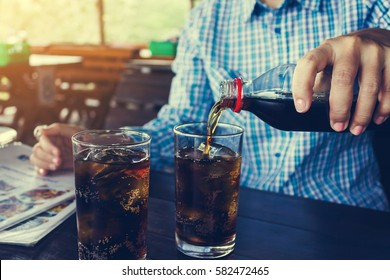 Women hand pour or fill drink in glass, double glass of soda on wooden table