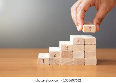 Women hand putting a wooden block on top and arranging wooden blocks stacking on wooden table  in the shape of a staircase, Business concept for growth success process.