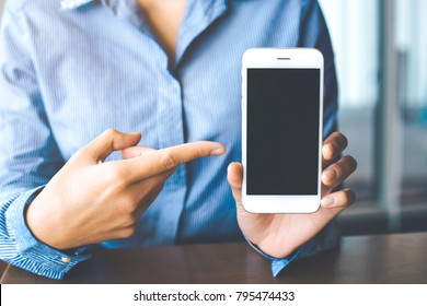 e96ddc30c65d9 Women hand show the white mobile phone at the blank screen in the office.