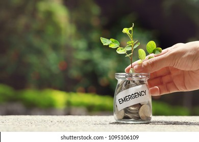 Women hand touching money jar with coins and emergency label, Saving for emergency concept.