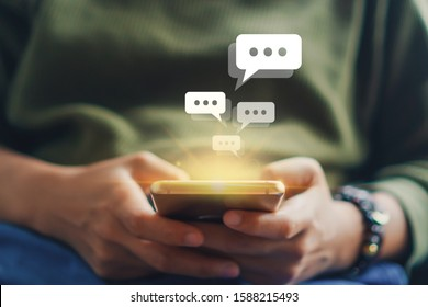 Women hand using smartphone typing, chatting conversation in chat box icons pop up. Social media maketing technology concept.Vintage soft color tone background.