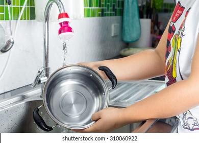women hand washing Pans In sink