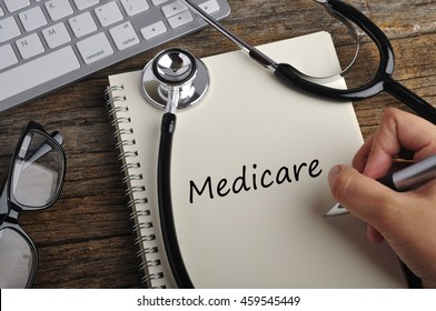 """Women Hand Write """"MEDICARE"""" On Note Book"""
