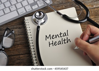 "Women Hand Write ""Mental Health"" On Note Book"